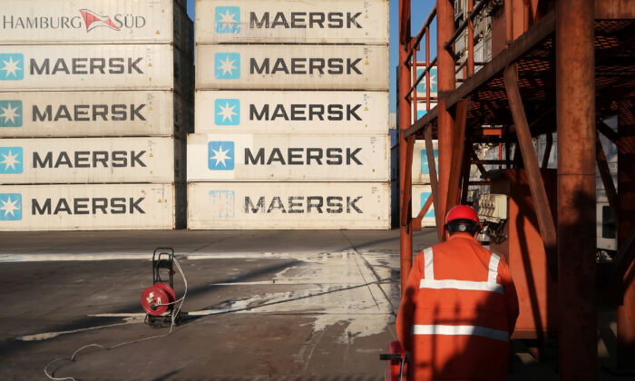 A worker is seen next to Maersk shipping containers at a logistics center near Tianjin port, in Tianjin, China on Dec. 12, 2019. (Yilei Sun/Reuters)