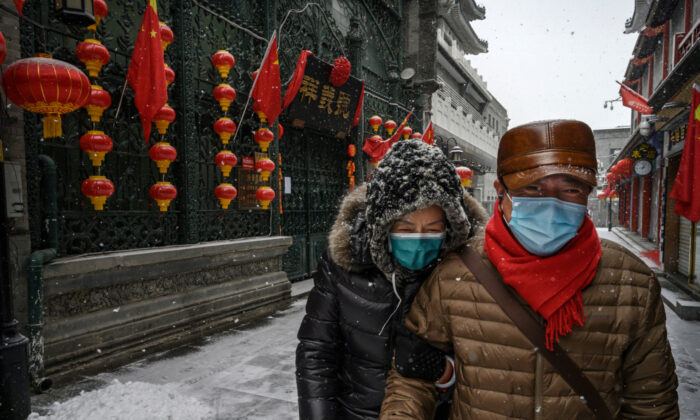 A Chinese couple wear protective masks as they walk during a snowfall in an empty and shuttered commercial street in Beijing, China, on Feb. 5, 2020. (Kevin Frayer/Getty Images)
