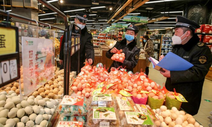 This photo taken on Feb. 20, 2020 shows market supervision administer checking eggs in a supermarket as they monitor the price of commodities during the COVID-19 coronavirus outbreak in Huaibei in China's eastern Anhui province. (STR/AFP via Getty Images)