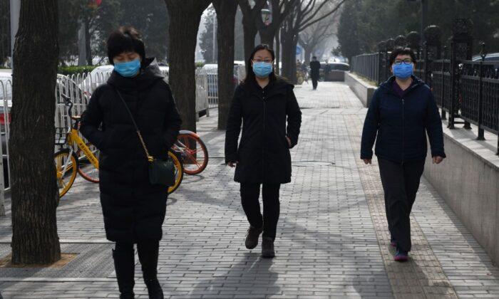 Women wear face masks as they walk on a street in Beijing on Feb. 21, 2020. (Greg Baker/AFP via Getty Images)