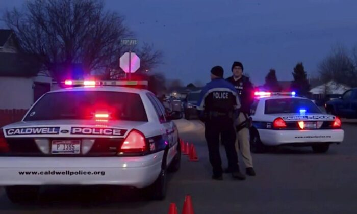 Police cars and officers are seen near the site of a shooting in Caldwell, Idaho, on Feb. 20, 2020. (KBOI/CBS 2 via AP)