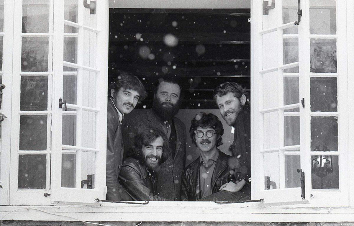 5 men looking out an open window