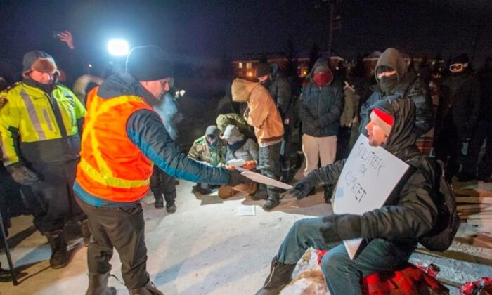 Police serve an injunction to protesters at a rail blockade in St. Lambert, south of Montreal, on Feb. 20, 2020. (Ryan Remiorz/The Canadian Press)