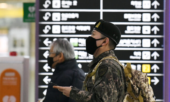 A South Korean soldier (R) wearing a face mask looks at train departure timetable at a railway station in the southeastern city of Daegu, South Korea, on Feb. 21, 2020. (JUNG YEON-JE/AFP via Getty Images)