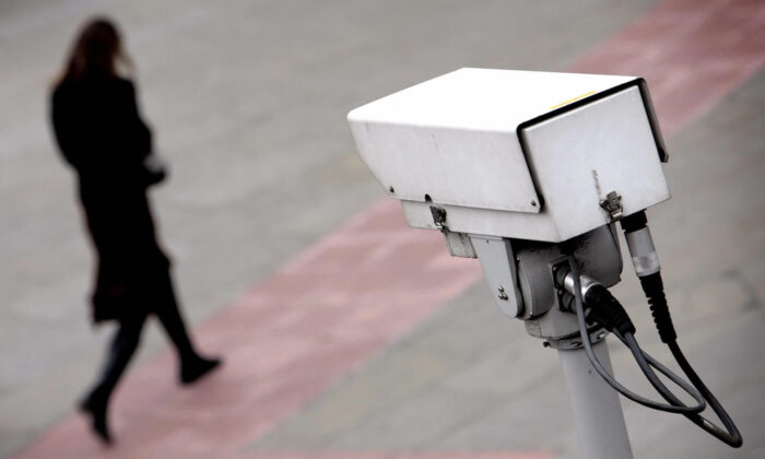 File photo of a security camera observing a woman. (Leon Neal/AFP via Getty Images)