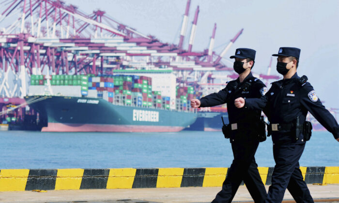 Police officers wearing face masks patrol at a container port in Qingdao in eastern China's Shandong Province, China on Feb. 19, 2020. (Chinatopix via AP)