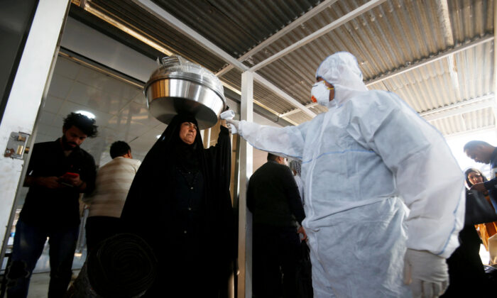 An Iraqi medical staff member checks a passenger's temperature, amid the new coronavirus outbreak, upon her arrival to Shalamcha Border Crossing between Iraq and Iran, on Feb. 20, 2020. (Essam al-Sudani/Reuters)