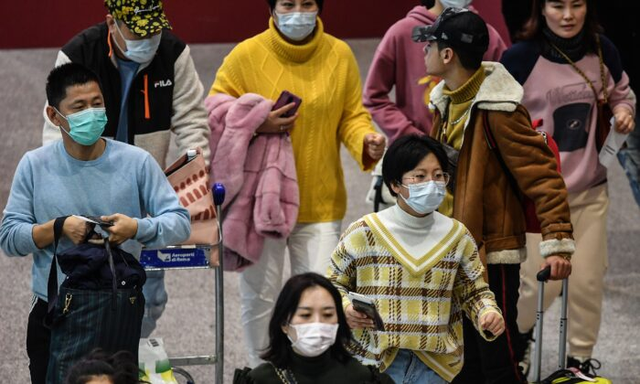 Passengers wearing respiratory masks walk across a terminal towards the check in counter at Rome's airport in Italy on Jan. 31, 2020. (Tiziana Fabi/AFP via Getty Images)