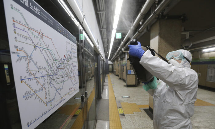 A worker wearing protective gears sprays disinfectant as a precaution against the coronavirus at a subway station in Seoul, South Korea, on Feb. 21, 2020. (Ahn Young-joon/AP Photo)