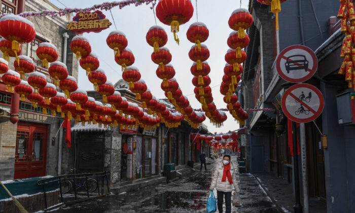 A Chinese woman wears a protective mask as she walks in a nearly empty and shuttered commercial street in Beijing on Feb. 7, 2020. (Kevin Frayer/Getty Images)
