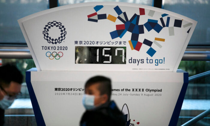 People wearing masks sit in front of a countdown clock for the Tokyo 2020 Olympics in Tokyo, on Feb. 18, 2020. (Jae C. Hong/AP Photo, File)