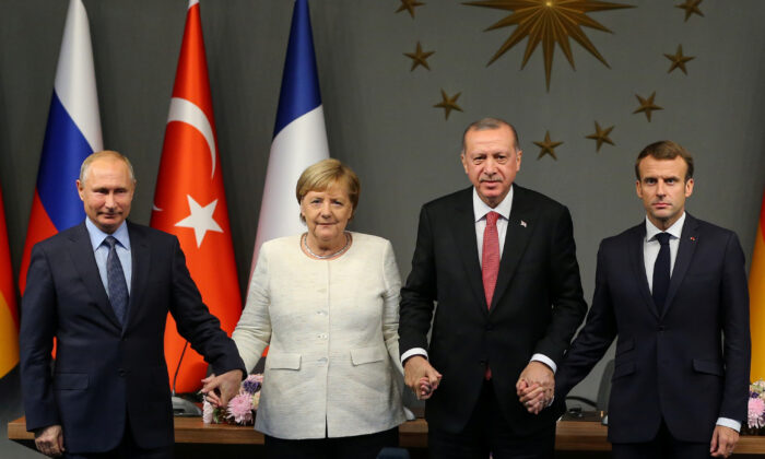 From left to right: Russian President Vladimir Putin, German Chancellor Angela Merkel, Turkish President Tayyip Erdogan, and French President Emmanuel Macron hold hands at a news conference after a Syria summit in Istanbul, Turkey, on Oct. 27, 2018. (Emrah Yorulmaz/Pool via REUTERS)