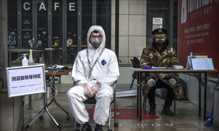 A Chinese guard wears a protective mask and suit as he waits to check temperatures and register people entering a building in a commercial area in Beijing on on Feb. 21, 2020. (Kevin Frayer/Getty Images)