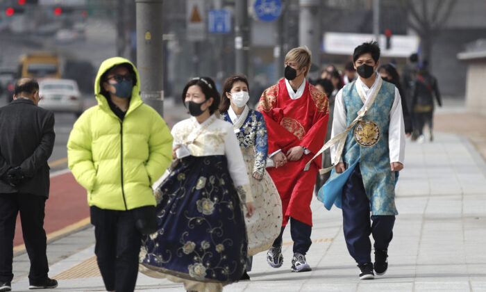 Visitors wearing face masks walk near the Gwanghwamun, the main gate of the 14th-century Gyeongbok Palace, and one of South Korea's well-known landmarks, in Seoul on Feb. 22, 2020. (Lee Jin-man/AP Photo)