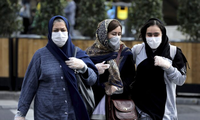 Women wear masks and gloves to help guard against the coronavirus in downtown Tehran, Iran on Feb. 23, 2020. (Ebrahim Noroozi/AP Photo)