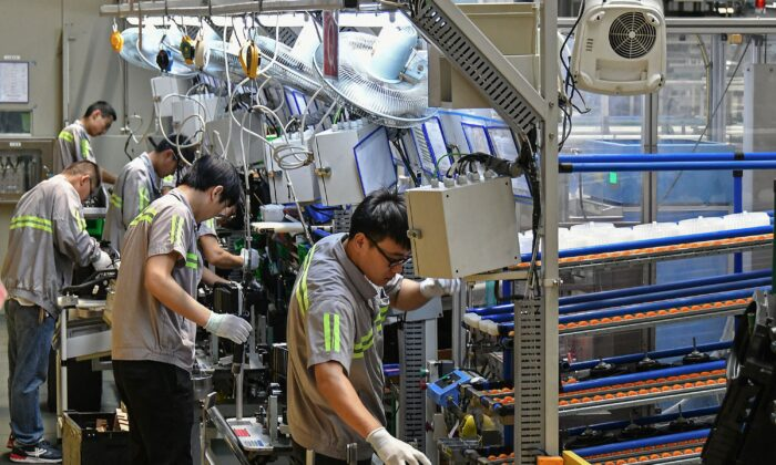 Employees work on an automobile air conditioning production line at a factory in Yantai in China's eastern Shandong Province on May 15, 2019. (STR/AFP via Getty Images)