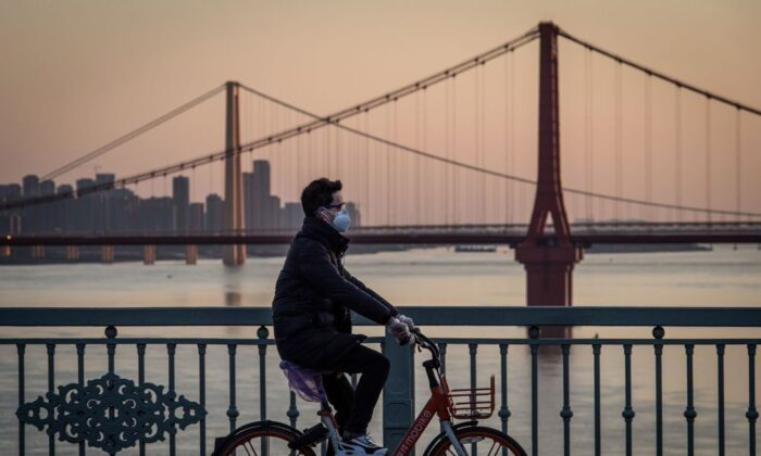 A man wearing a protective face mask rides a bicycle in Wuhan, China, on Feb. 17, 2020. (STR/AFP via Getty Images)