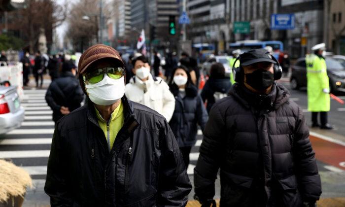 People wear masks to prevent the novel coronavirus walks along the street in Seoul, South Korea, on Feb. 22, 2020. (Chung Sung-Jun/Getty Images)