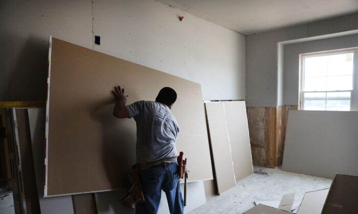 A worker hangs drywall in in Hamden, Conn., on Aug. 2, 2017. In a controversial decision Judge Carlos Murguia threw out the convictions of two illegal aliens from Mexico, whom a jury found guilty of conspiring to encourage illegal aliens to remain in the United States through employment at a drywall company. (Spencer Platt/Getty Images)