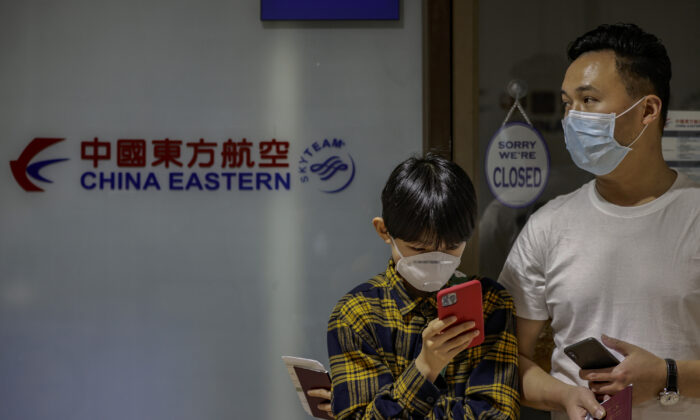 Chinese nationals, whose flight was cancelled after the Philippine government imposed travel restrictions to and from China amid the outbreak of the novel coronavirus, wait outside the closed ticketing office of China Eastern Airlines at the Ninoy Aquino International Airport in Manila, Philippines, on Feb. 3, 2020. (Ezra Acayan/Getty Images)