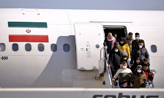 Passengers disembarking from an Iranian plane in the airport in Najaf, Iraq, on Feb. 21, 2020. (Anmar Khalil/AP Photo)