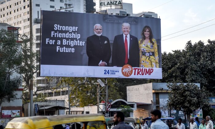 Commuters and pedestrians pass below a billboard depicting U.S. President Donald Trump (C), his wife Melania Trump (R) and India's Prime Minister Narendra Modi (L), in Ahmedabad, India, on Feb. 18, 2020. (Sam Panthaky/AFP via Getty Images)