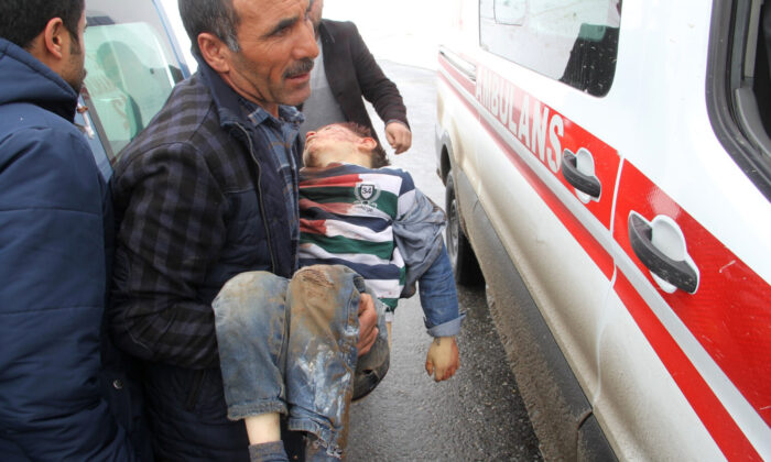 A man carries a wounded boy to an ambulance after an earthquake hit villages in Baskale town in Van province, Turkey, at the border with Iran, on Feb. 23, 2020. (IHA via AP)