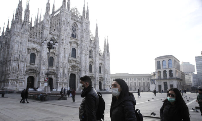 People wearing sanitary masks walk past the Duomo gothic cathedral in Milan, Italy, on Feb. 23, 2020. (Luca Bruno/AP Photo)