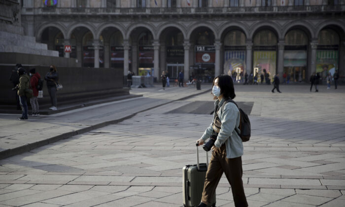 A woman wearing a sanitary mask pushes a trolley in Duomo square, Milan, Italy, on Feb. 23, 2020. (Luca Bruno/AP Photo)