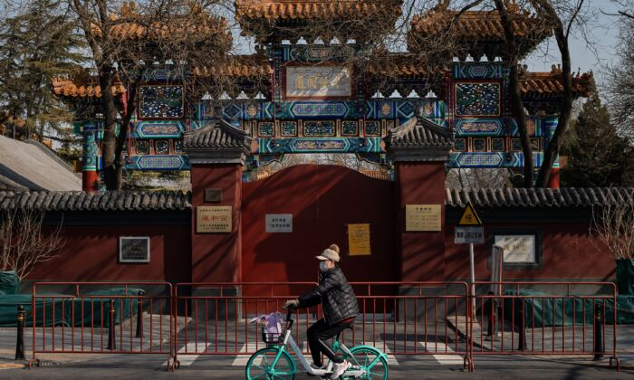 A woman wearing a protective facemask to protect against the COVID-19 coronavirus cycles in front of the Lama Temple in Beijing, China on Feb. 23, 2020. (NICOLAS ASFOURI/AFP via Getty Images)