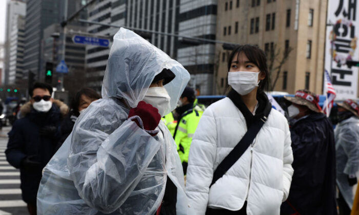 People wear masks to prevent the novel coronavirus walk along the street in Seoul, South Korea, on Feb. 22, 2020. (Chung Sung-Jun/Getty Images)