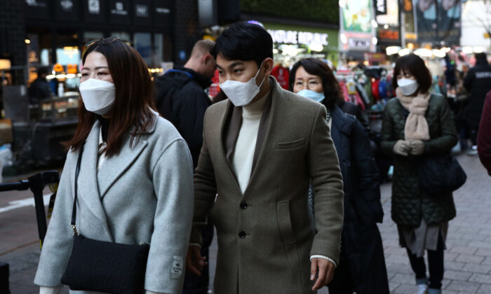 People wearing masks to prevent the novel coronavirus walk along the Myungdong shopping district in Seoul, South Korea, on Feb. 23, 2020. (Chung Sung-Jun/Getty Images)