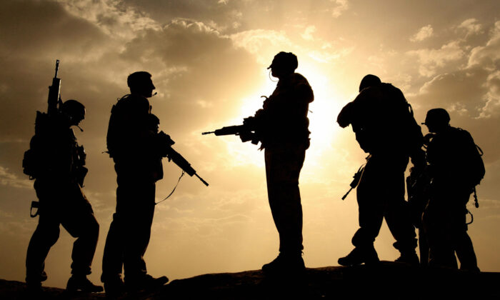 British soldiers from 21 Air Assault Battery Royal Artillery are silhouetted against the sky as they provide security for a meeting with the Afghan National Police at the fortress Qala-e-Bost in Lashkar Gah, Helmand Province, on May 17, 2006. (John D. McHugh/AFP via Getty Images)