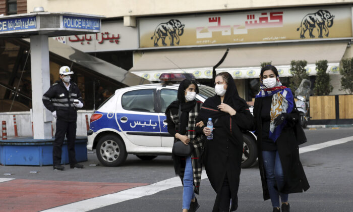 A policeman and pedestrians wear masks to help guard against the coronavirus, in downtown Tehran, Iran, on Feb. 23, 2020. (Ebrahim Noroozi/AP Photo)