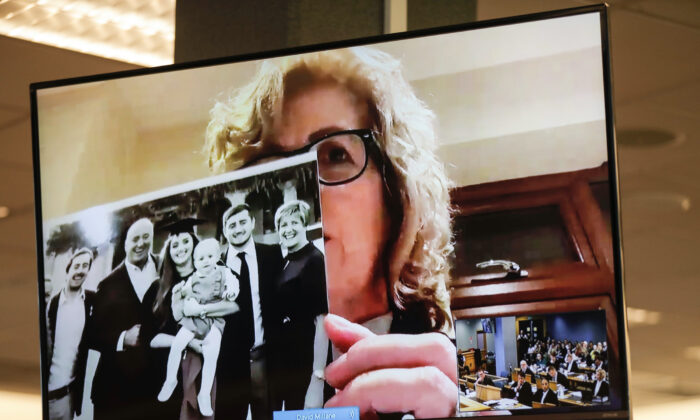 Gillian Millane, mother of murdered British backpacker Grace, holds up a photo during her victim impact statement via video link from England, at the sentencing of the man found guilty of her murder at the Auckland High Court in Auckland, New Zealand on Friday, Feb. 21, 2020. (Dean Purcel/New Zealand Herald via AP)