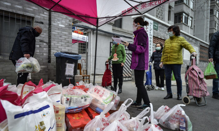 Residents wearing protective face masks collect foods distributed by volunteers outside their home in Wuhan in central China's Hubei Province, on Feb. 22, 2020. (Chinatopix via AP)