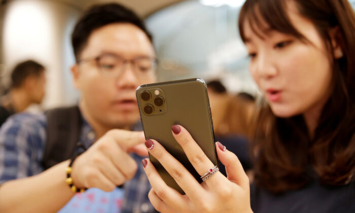 A customer touches an Apple's new iPhone 11 Pro Max after it went on sale at the Apple Store in Beijing, China, on Sept. 20, 2019. (Jason Lee/Reuters)