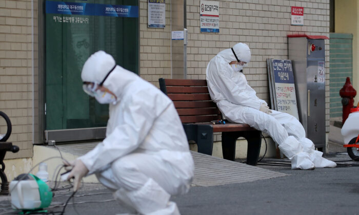 A medical worker takes a rest outside a hospital in Daegu, South Korea, on Feb. 23, 2020. (Yonhap via Reuters)