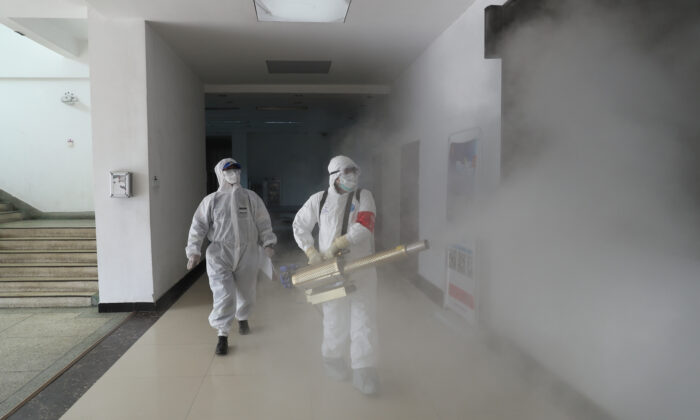Volunteers in protective suits disinfect a residential compound in Wuhan, the epicenter of the Novel Coronavirus outbreak, in Hubei Province in China on Feb. 22, 2020. (China Daily via Reuters)