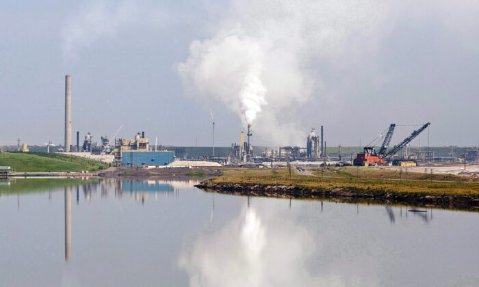 An oil sands facility is reflected in a tailings pond near Fort McMurray, Alta., in a file photo. (The Canadian Press/Jeff McIntosh)
