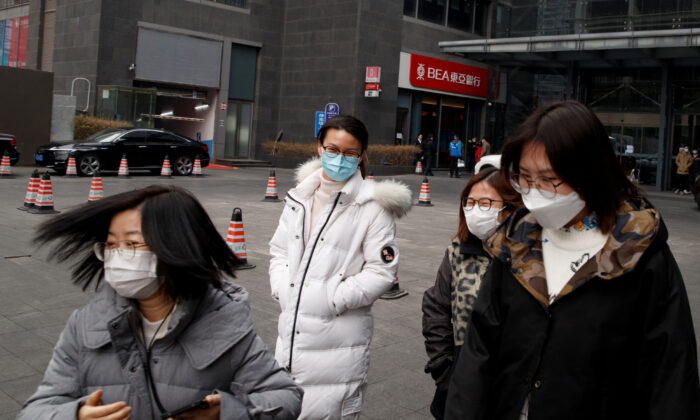 People wear face masks as they leave an office building in the Central Business District in Beijing as the country is hit by an outbreak of the novel coronavirus, China on Feb. 24, 2020. (Thomas Peter/Reuters)