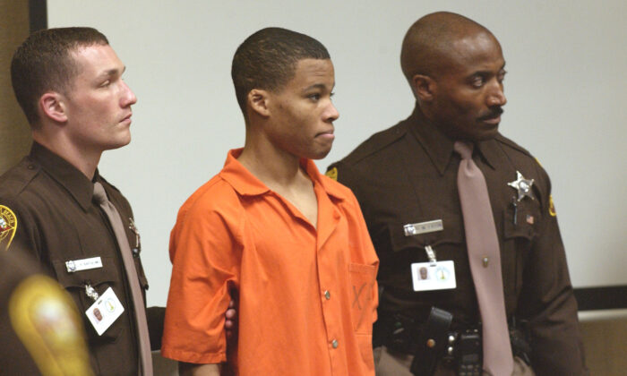 Then-sniper suspect Lee Boyd Malvo (C) is brought into court to be identified by a witness during the murder trial in Virginia Beach Circuit Court in Virginia Beach, Va., on Oct. 22, 2003. (Davis Turner-Pool/Getty Images)