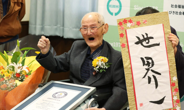 112-year-old Japanese man Chitetsu Watanabe poses next to calligraphy reading in Japanese 'World Number One' after he was awarded as the world's oldest living male in Joetsu, Niigata prefecture on Feb. 12, 2020. (Photo by Japan Pool/JIJI PRESS/AFP via Getty Images)