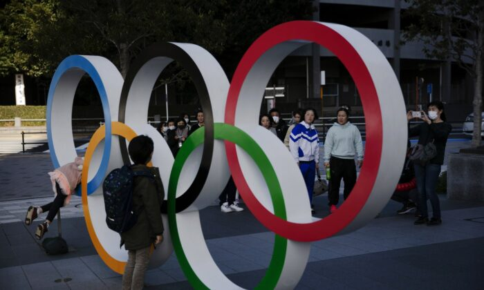 People wait in line to take pictures with the Olympic rings near the New National Stadium in Tokyo, Japan, on Feb. 23, 2020. (Jae C. Hong/AP Photo)
