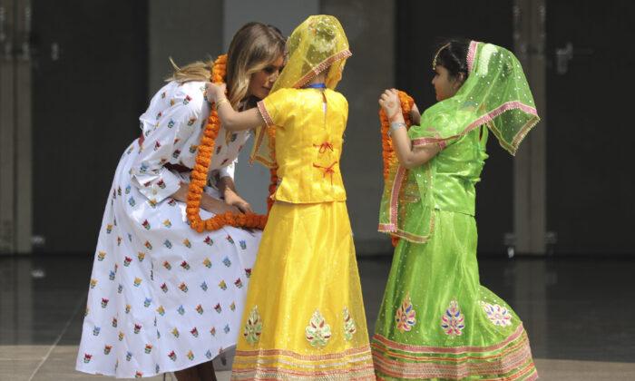 U.S. First Lady Melania Trump is garlanded by two children at Sarvodaya Co-Educational Senior Secondary School in New Delhi, India, on Feb. 25, 2020. (Altaf Qadri/AP Photo)
