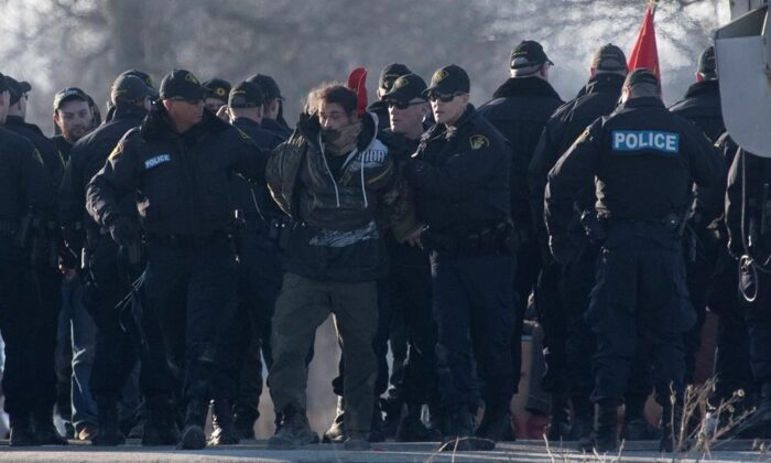 Ontario Provincial Police officers make arrests at a rail blockade in Tyendinaga Mohawk Territory, near Belleville, Ont., on Feb. 24, 2020, as they protest in solidarity with Wet'suwet'en Nation hereditary chiefs attempting to halt construction of a natural gas pipeline on their traditional territories. (The Canadian Press/Adrian Wyld)