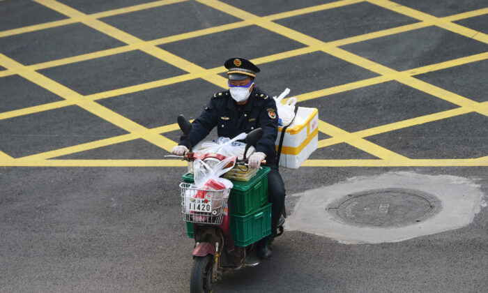 A man wearing a face mask rides a bike filled with food supplies in Wuhan, the epicenter of the Novel Coronavirus outbreak, Hubei province, China, on Feb. 24, 2020. (Stringer/Reuters)