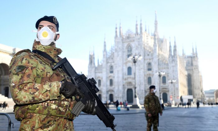 Military officers wearing face masks stand outside Duomo cathedral, closed by authorities due to a coronavirus outbreak, in Milan, Italy, on Feb. 24, 2020. (Flavio Lo Scalzo/Reuters)
