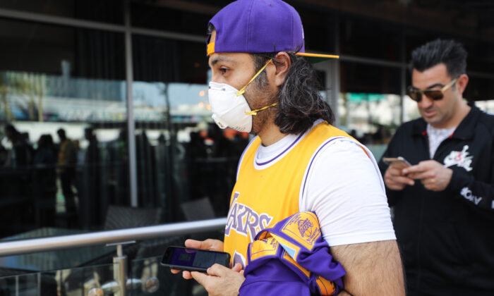 A fan wears a protective mask as people wait in line to attend the 'Celebration of Life for Kobe and Gianna Bryant' memorial service at Staples Center in Los Angeles on Feb. 24, 2020. (Mario Tama/Getty Images)