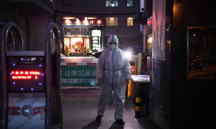 A security guard wears protective clothing as a preventive measure against the COVID-19 coronavirus as he stands at the entrance of a restaurant in Beijing on Feb. 25, 2020. (Greg Baker/AFP via Getty Images)